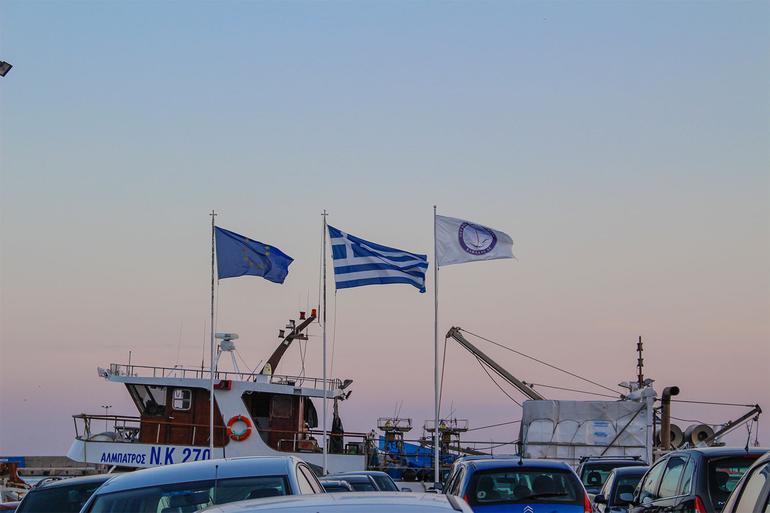 Sunset at the harbor in City of Drama, Greece with the flags